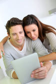 Cheerful couple websurfing on internet with tablet — Stock Photo
