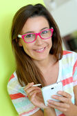 Brunette girl with eyeglasses using smartphone — Stock Photo