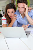 Couple looking at bank account with shocked expression — Stock Photo