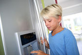 Young boy drinking water from fridge — Stock Photo