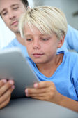 Father and son using digital tablet at home — Stock Photo