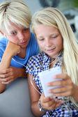 Tieners gebruikend smartphone met koptelefoon — Stockfoto