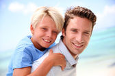 Daddy giving piggyback ride to son by the beach — Stock Photo
