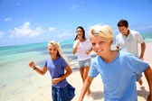 Cheerful family running on a sandy beach — Stock Photo
