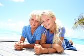 Blond teenagers laying on pool deck in summer — Stock Photo