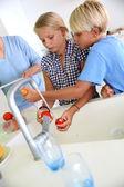 Kinder waschen frische tomaten für salate — Stockfoto