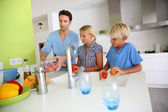 Father with kids preparing tomatoe salad — Stock Photo