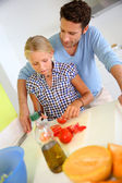 Man with young girl preparing meal in kitchen — Stock Photo