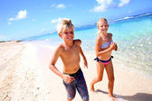 Kids running on a sandy beach in Caribe — Stock Photo