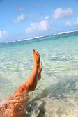 Closeup of woman's feet in Caribbean sea — Stock Photo