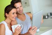 Veselý pár pomocí tabletu v době snídaní — Stock fotografie