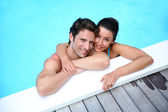 Portrait of cheerful couple in swimming-pool — Stock Photo