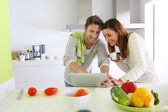 Couple in home kitchen looking for lunch recipe — Stock Photo