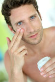 Handsome man applying moisturizing cream — Stok fotoğraf