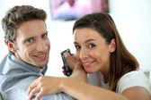 Smiling couple watching movie on Tv — Stock Photo