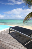 Infinity pool with deck chair by the beach — Stock Photo