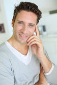 Smiling handsome guy with hand on chin — Stock Photo
