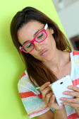Girl with pink eyeglasses connected on internet — Stock Photo
