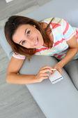 Vue supérieure de la femme dans le canapé à l'aide de smartphone — Photo
