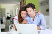 Couple at home sitting in front of laptop — Stock Photo