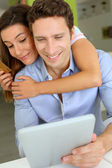Cheerful couple with tablet shopping on internet — Stock Photo