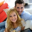 Stock Photo: Cheerful young couple doing online shopping with tablet