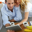 Young couple websurfing with tablet in home kitchen — Stock Photo #27920623