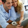 Stock Photo: Young couple websurfing with tablet in home kitchen