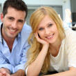 Cheerful young couple sitting in front of modern house — Stock Photo #27920891