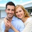 Cheerful young couple sitting in front of modern house — Stock Photo #27920893