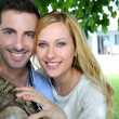 Cheerful young couple standing under tree — Stock Photo #27920897