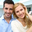Cheerful young couple sitting in front of modern house — Stock Photo #27920899