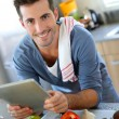 Closeup of smiling man in kitchen using tablet — Stock Photo #27921011