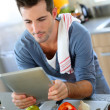 Closeup of smiling man in kitchen using tablet — Stock Photo