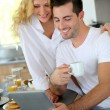 Young couple using digital tablet at breakfast time — Stock Photo #27921269