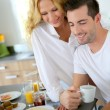 Young couple using digital tablet at breakfast time — Stock Photo