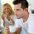 Portrait of young man holding cup of coffee — Stock Photo