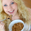 Smiling blond girl eating cereals for breakfast — Stock Photo #27921381
