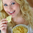 Smiling woman eating potato chips — Stock Photo #27921407