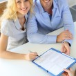 Cheerful couple signing property contract with real-estate agent — Stock Photo