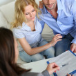 Cheerful couple signing property contract with real-estate agent — Stock Photo #27921541