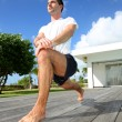 Young man doing stretching exercises by the pool — ストック写真