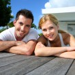 Young couple relaxing on pool deck after exercising — Stock Photo #27921833
