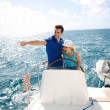 Young couple navigating on a yacht in caribbean sea — Stock Photo