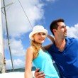 Smiling rich young couple on a sailboat in Caribbean sea — Стоковая фотография