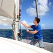 Stock Photo: Young mlifting sail of catamarduring cruising