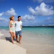 Young couple walking on a sandy beach — Stock Photo
