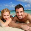 Cheerful young couple laying on a sandy beach — Stock Photo