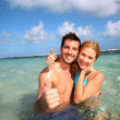 Couple in a caribbean lagoon showing thumbs up — Stock Photo #27922577