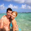 Couple in a caribbean lagoon showing thumbs up — Stock Photo